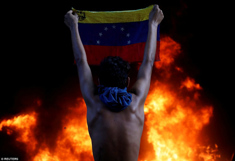 A protester holds the Venezuelan flag as a bank branch - housed in the magistracy of the Supreme Court of Justice - burns during a rally against the country's president, Nicolás Maduro, in the capital, Caracas, on June 12