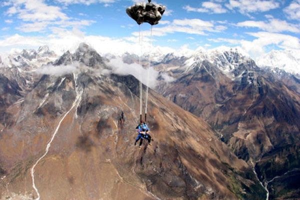 The parachute deploys as the tandem skydivers are about to land at a drop zone located in the middle of the Himalaya Mountains.