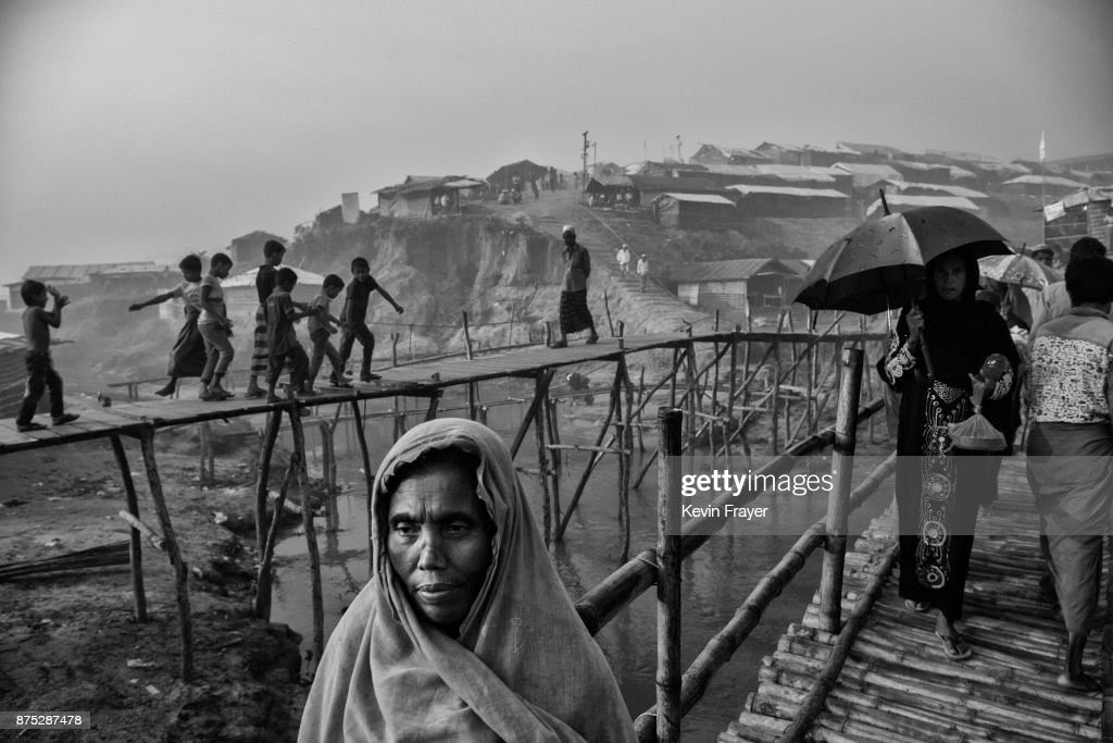 COX'S BAZAR, BANGLADESH - OCTOBER 27: Rohingya refugees walk on makeshift bamboo bridges on October 27, 2017 at the Kutupalong refugee camp near Cox's Bazar, Bangladesh. More than 600,000 Rohingya refugees have flooded into Bangladesh to flee an offensive by Myanmar's military that the United Nations has called 'a textbook example of ethnic cleansing'. The refugee population continues to swell further, with thousands more Rohingya Muslims making the perilous journey on foot toward the border, or paying smugglers to take them across by water in wooden boats. Hundreds are known to have died trying to escape, and survivors arrive with horrifying accounts of villages burned, women raped, and scores killed in the 'clearance operations' by Myanmar's army and Buddhist mobs that were sparked by militant attacks on security posts in Rakhine state on August 25, 2017. What the Rohingya refugees flee to is a different kind of suffering in sprawling makeshift camps rife with fears of malnutrition, cholera, and other diseases. Aid organizations are struggling to keep pace with the scale of need and the staggering number of them - an estimated 60 percent - who are children arriving alone. Bangladesh, whose acceptance of the refugees has been praised by humanitarian officials for saving lives, has urged the creation of an internationally-recognized 'safe zone' where refugees can return, though Rohingya Muslims have long been persecuted in predominantly Buddhist Myanmar. World leaders are still debating how to confront the country and its de facto leader, Aung San Suu Kyi, a Nobel Peace Prize laureate who championed democracy, but now appears unable or unwilling to stop the army's brutal crackdown. During a recent visit to Myanmar, U.S Secretary of State Rex Tillerson called for a 'credible' probe into human rights violations against the Rohingya but said he would advise against full sanctions on the country.