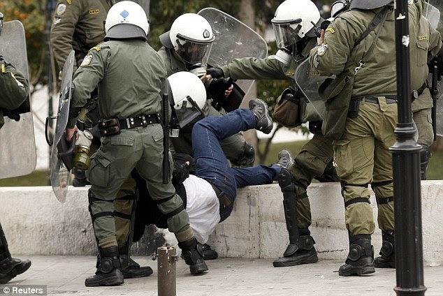 Έφερε τα κάτω: Αστυνομία καταπιαστεί με ένα διαδηλωτή.  Οι ηγέτες της ΕΕ έχουν προστεθεί λάδι στη φωτιά με τη διαταγή Ελλάδα να βρει έναν άλλο 325million ευρώ σε περικοπές