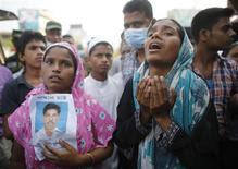 Los trabajadores textiles de Bangladesh expresaron su malestar el viernes quemando coches y enfrentándose con la policía mientras la cifra de muertos superaba las 300 personas después del colapso de un edificio que albergaba fábricas de ropa a bajo coste para marcas occidentales. En la imagen, dos mujeres muestran la foto de un familiar trabajador textil que se cree quedó atrapado en los escombros del derrumbe del edificio Rana Plaza, en Savar, a 30 kilómetros de Dacca, el 26 de abril de 2013. REUTERS/Andrew Biraj