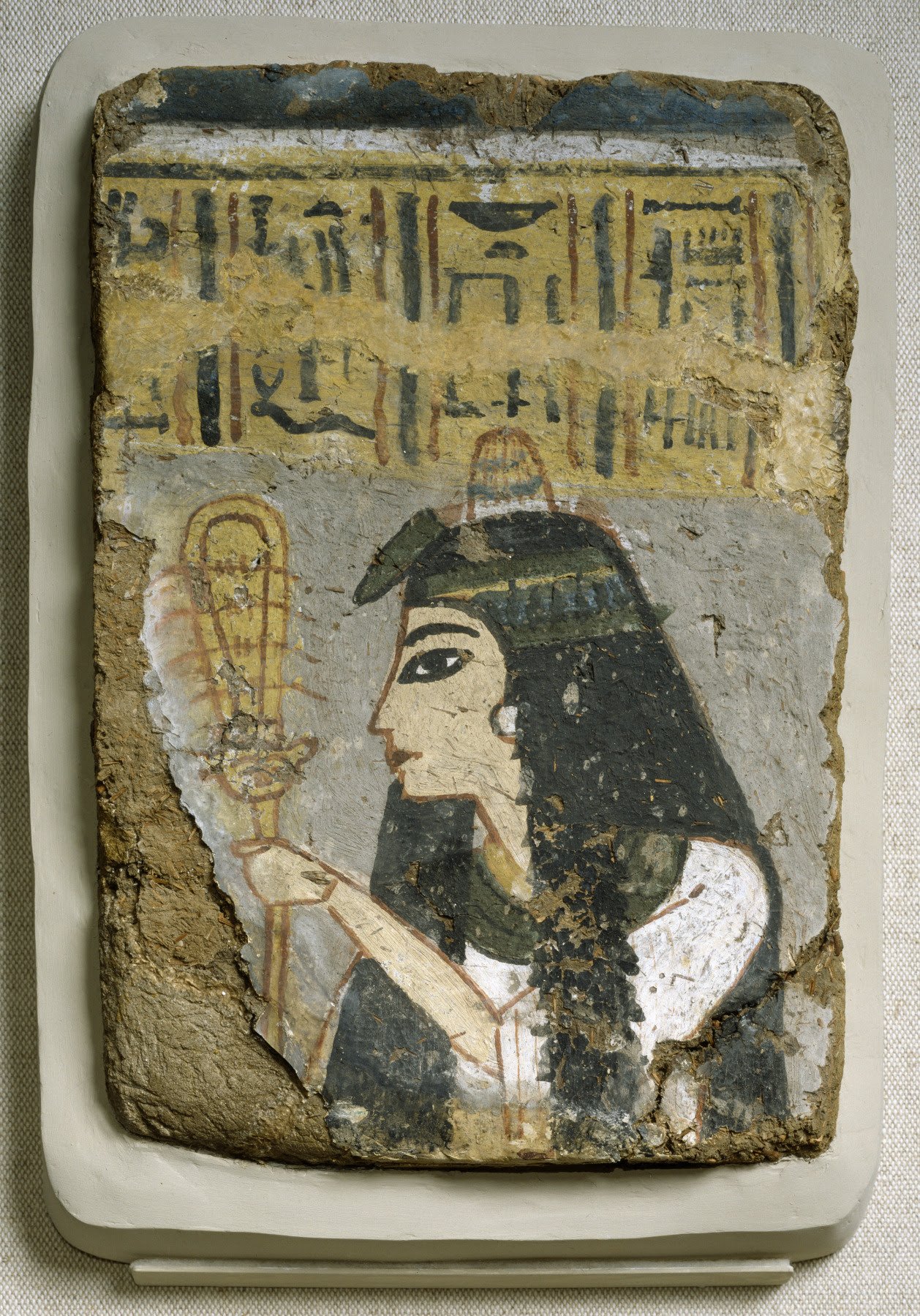 Ancient Egyptian Wall Painting: Woman Holding a Sistrum, between circa 1250 and circa 1200 BC (New Kingdom).  The woman in this fragmentary painting from a tomb wall has a wig of long, full hair, held in place by a flowered headband and topped with an ointment cone, a perfumed substance placed on wigs that gave off a fragrant aroma as it melted. A lotus blossom adorns the front of the headband. She holds a rattle called a sistrum, which women often played during temple ceremonies. What remains of the inscription suggests that she may have served with the temple staff of the god Amen.  Currently located at the Walters Art Museum, Baltimore, USA