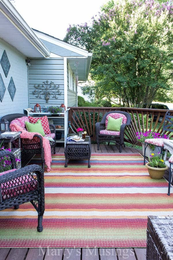 Try these 5 deck decorating ideas on a budget to create a gorgeous outdoor room with an area rug, throw pillows, flowers and inexpensive accessories.