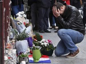 Homem se emociona diante de objetos de tributo deixados em frente à cafeteria Carillon, em Paris, onde um dos ataques terroristas ocorreu (Foto: Thibault Camus/AP)