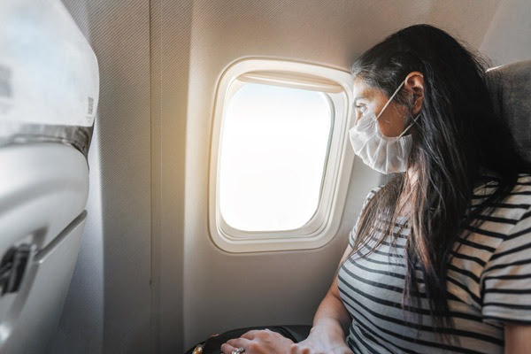 woman wearing mask looking out airplane window