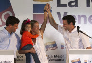 Opposition politician Leopoldo Lopez, puts his arm around the waist of his wife Lilian Tintori as she holds their daughter Manuela, 2, and raises her left hand with presidential candidate Henrique Capriles Radonski at a news conference in Caracas, Venezuela, Tuesday Jan 24, 2012. Lopez bowed out of Venezuela's presidential race on Tuesday, saying he will support front-runner Capriles. The announcement gives a significant boost to Capriles, who has a commanding lead in the polls ahead of the Feb. 12 opposition primary, which will choose a single challenger to face President Hugo Chavez in the Oct. 7 presidential election. (AP Photo/Ariana Cubillos))