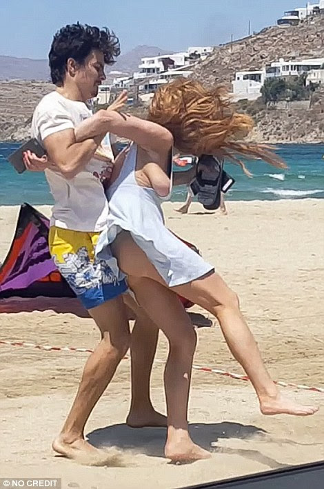 He grabbed her after she threw his phone out of their vehicle