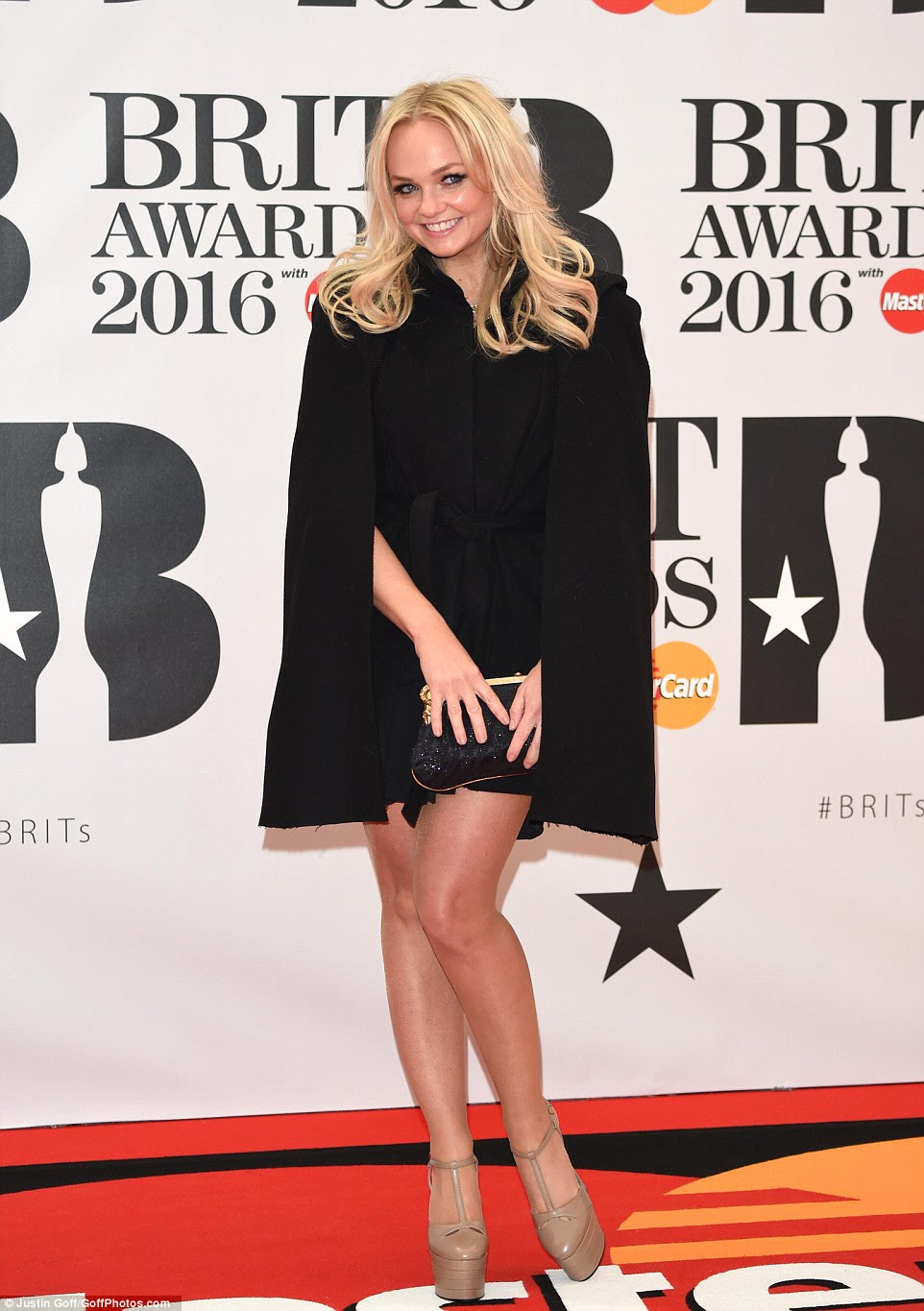 Chic Spice! Emma looked sensational and a world away from her Baby Spice days in a caped black dress and towering taupe heels