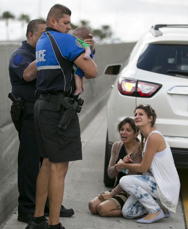 O policial Amauris Bastidas ajuda a socorrer o bebê de cinco meses Sebastian de la Cruz, que parou de respirar enquanto era levado de carro por sua tia em uma estrada na Califórnia (Foto: The Miami Herald, Al Diaz/AP)