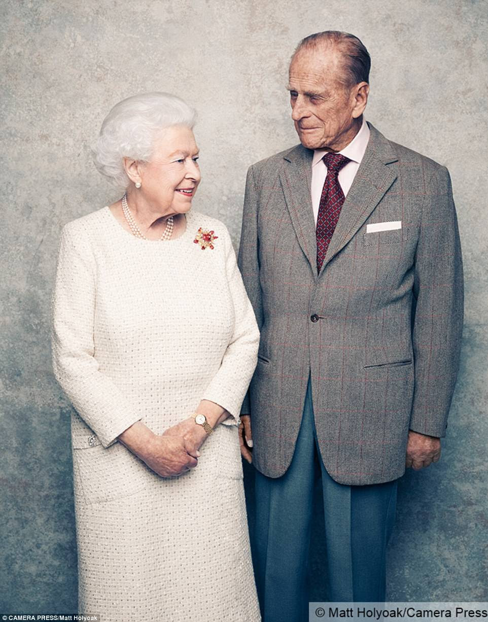 Remarkable milestone: Another photograph sees the Queen, who wears a cream day dress by Angela Kelly, turning affectionately towards her husband