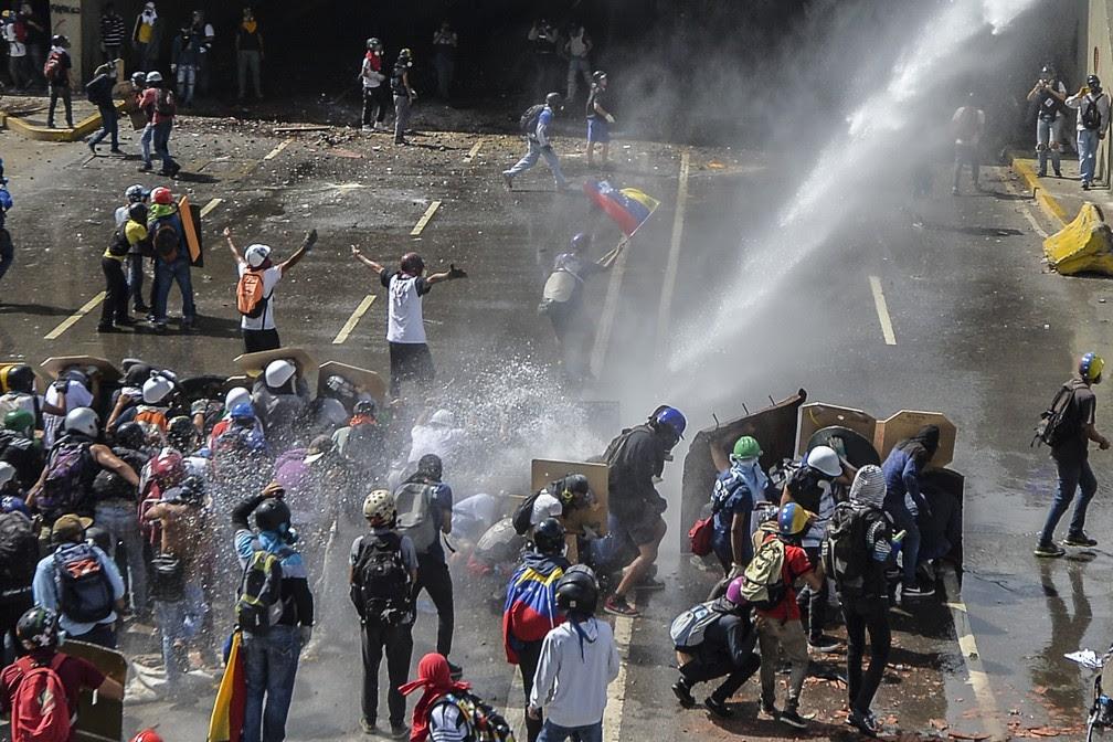 Oposição e forças de segurança da Venezuela entram em confronto durante manifestação nesta sexta-feira (26) em Caracas (Foto: LUIS ROBAYO / AFP)