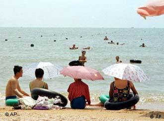 Chinese relax on a public beach at Beidaihe, a seaside resort east of Beijing, Sunday, Aug. 6, 2000. This quiet seaside haven is where President Jiang Zemin and other Chinese leaders come for a few weeks each summer to escape the muggy capital 150 miles to the west and hammer out policies between dips in the polluted, green-blue Bohai Sea. (AP Photo/John Leicester)