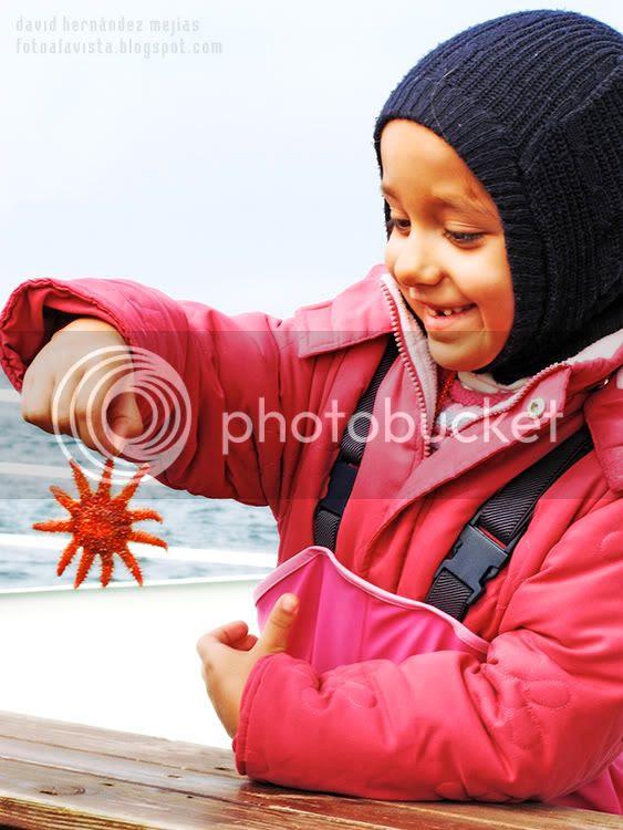 Niña en un barco sujetando en la mano una estrella de mar