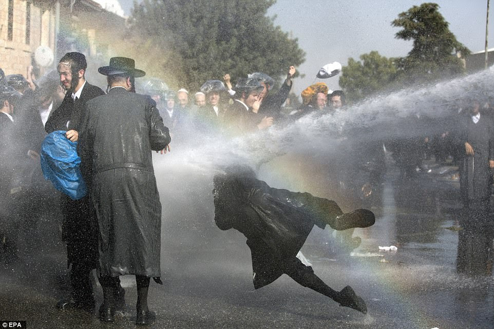 Israeli police use water cannon to disperse Ultra-Orthodox Jewish demonstrators blocking a main junction as they protest against army recruitment in Jerusalem on Sunday