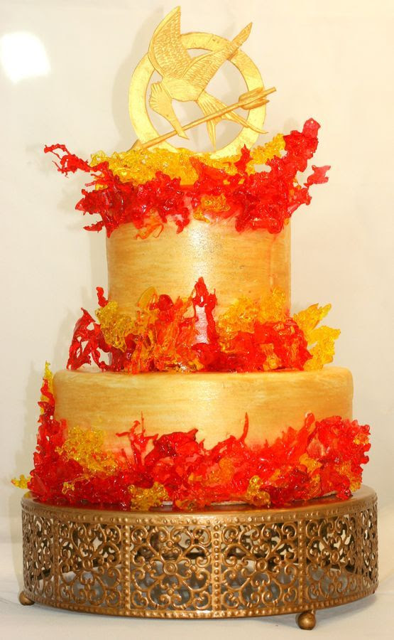 Boiled sugar flames with a gum paste topper.  Cake is handpainted in gold, orange and red.  Made for Hunger Games Challenge.