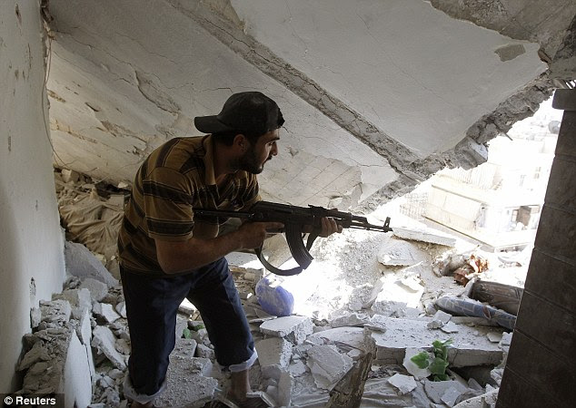 Taking aim: A Free Syrian Army fighter holds his rifle as he walks through an apartment destroyed by a tank shell during clashes with Syrian Army soldiers in the Salah al-Din neighbourhood in central Aleppo