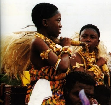 Ashanti Royal girls being carried shoulder high wearing regal Kente cloths