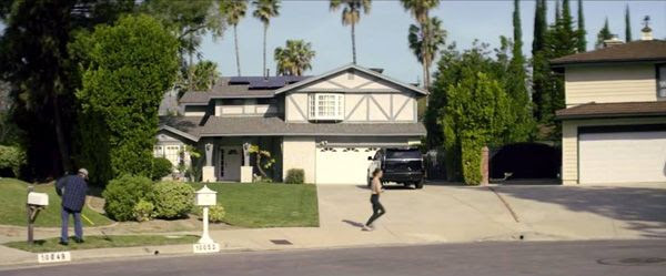A screenshot of me raking the grass in a peaceful neighborhood at the beginning of LET ME IN - WE ARE HERE.