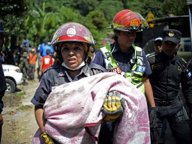 Criança é carregada no resgate de vítimas de um deslizamento de terra na Guatemala nesta sexta-feira (2) (Foto: AFP PHOTO / Johan ORDONEZ)
