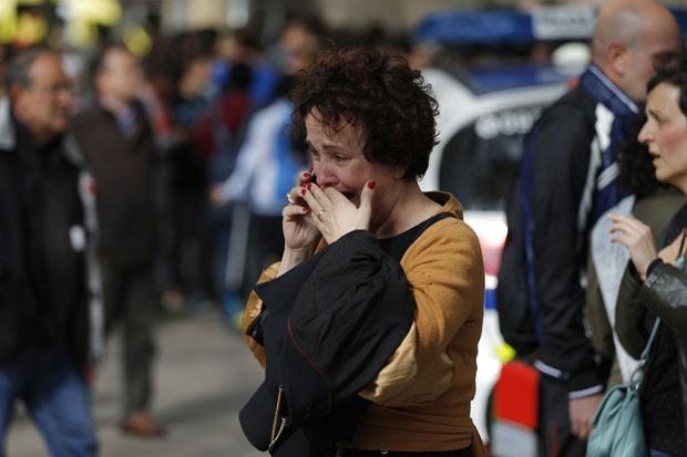 Mulher chora ao telefone após saber de ataque em escola em Barcelona; um professor morreu e quarto pessoas ficaram feridas nesta segunda-feira (20) (Foto: Emilio Morenatti/AP)