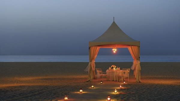 lantern lit beach dinner beneath white gazebo