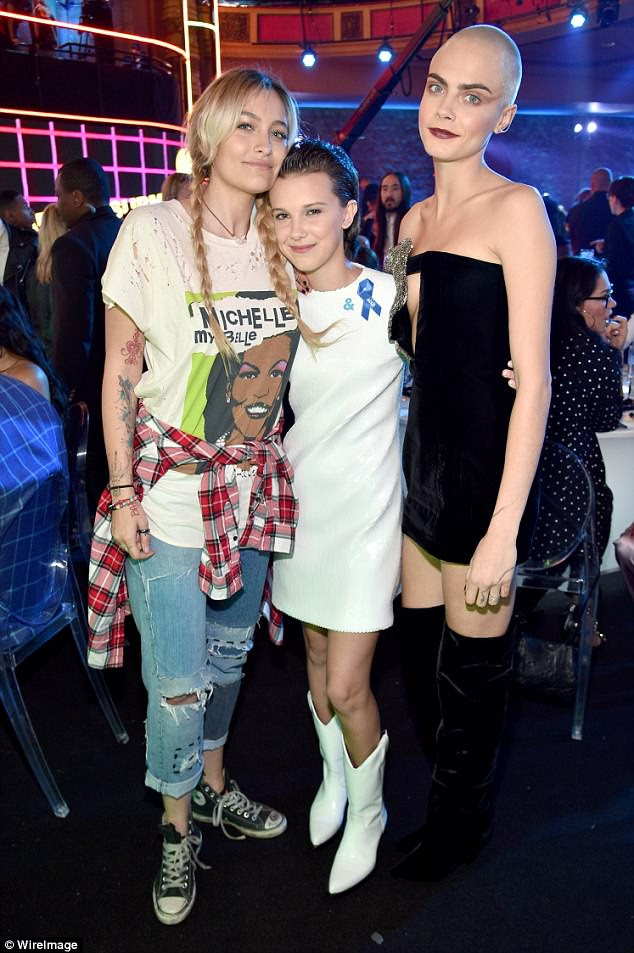Glammed up:The contrast was extremely noticeable once Paris posed with Stranger Things actress Millie Bobby Brown and model Cara Delevingne