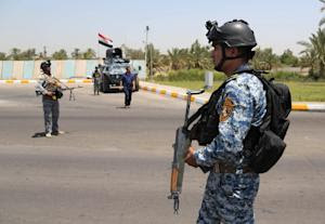 Iraqi federal policemen stand guard at a checkpoint …