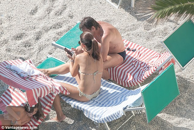 The married couple look at a phone from their sun beds during their holiday in Savona