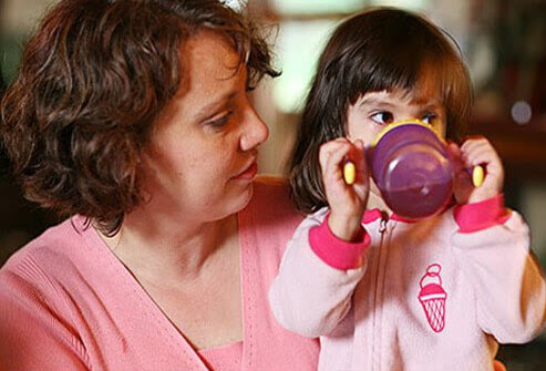 A young girls drinking out of sippy cup.
