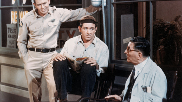 "Andy Griffith, left, Lindsey, center, and Howard McNear sit outside a barber shop in a still from ""The Andy Griffith Show"" around 1966."