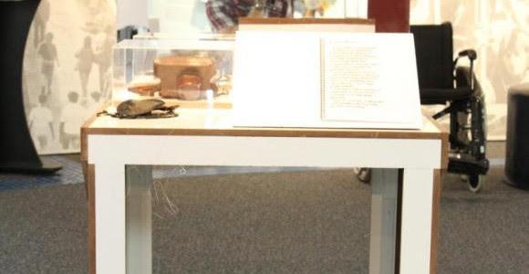 Foto de uma das áreas da exposição, com uma mesa. Nela. há uma encadernação aberta, aparada por um suporte