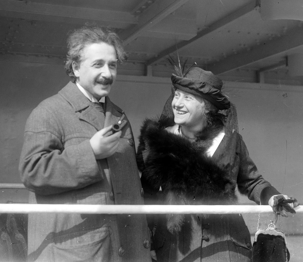 Photograph of Albert Einstein with his wife Elsa.  Einstein is pictured holding a pipe.  Both are wearing long coats.