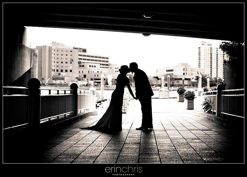 bride and groom kissing under a bridge on the tampa riverwalk