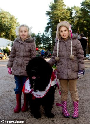 Jessica and Eleanor Connor follow a Newfoundland dog