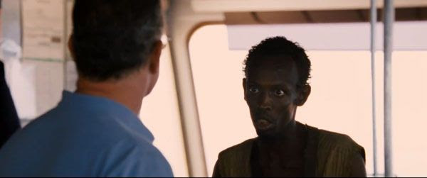 A Somali pirate confronts Captain Richard Phillips aboard the bridge of the Maersk Alabama in CAPTAIN PHILLIPS.
