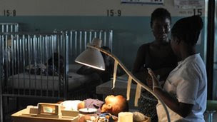 A toddler in hospital is tended by two women, Bong County, Liberia, 9 April 2012