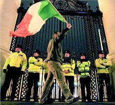 Διαδηλωτής ανεµίζει την ιρλανδική σηµαία έξω από το υπουργείο Οικονοµικών χθες στο Δουβλίνο. Χθες η Ιρλανδία  έγινε η δεύτερη ευρωπαϊκή χώρα που προσέφυγε στον µηχανισµό στήριξης της Ε.Ε. της ΕΚΤ και του ΔΝΤ