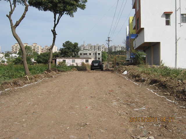 This 21 feet wide road from the Temples to Urbangram Kirkatwadi is under construction - at the end of the road, on the hills, you can see DSK Vishwa