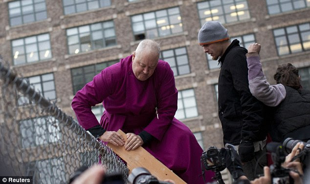Defiant: Retired Episcopal bishop George E. Packard is pictured climbing a ladder to illegally enter Duarte Square during an Occupy Wall Street march in New York City. He was promptly arrested for his actions