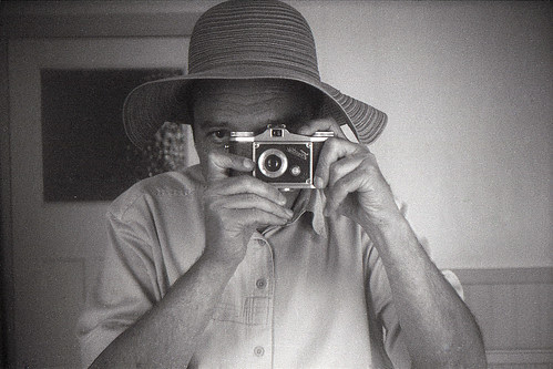 reflected self-portrait with Finetta camera and floppy hat by pho-Tony