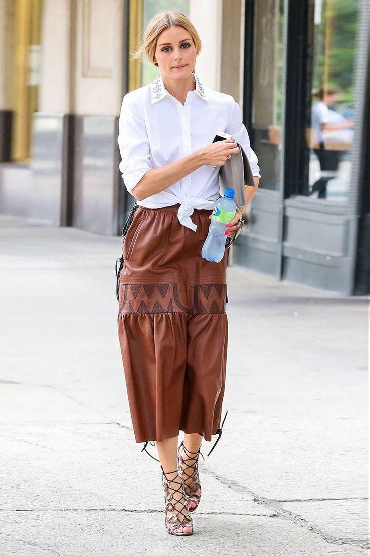 Olivia Palermo Siguiendo la tendencia cowboy en claveladylike,Olivia Palermofue vista paseando por el SoHo neoyorquino con una faldamidivintagede cuero marrón con cordones a los lados y bordados de estilowestern. Completó el look con una camisa anudada con pedrería en el cuello deAnn Taylor, un bolso gris perla y unas sandalias de piel de serpiente y finas tiras deAquazzura.