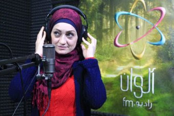A woman in a scarf touches her headphones as she speaks into a microphone.
