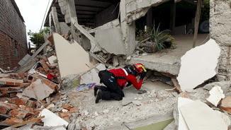 Els equips de rescat intenten passar entre la runa d'un dels edificis afectats a San Pablo de Manta (Reuters)