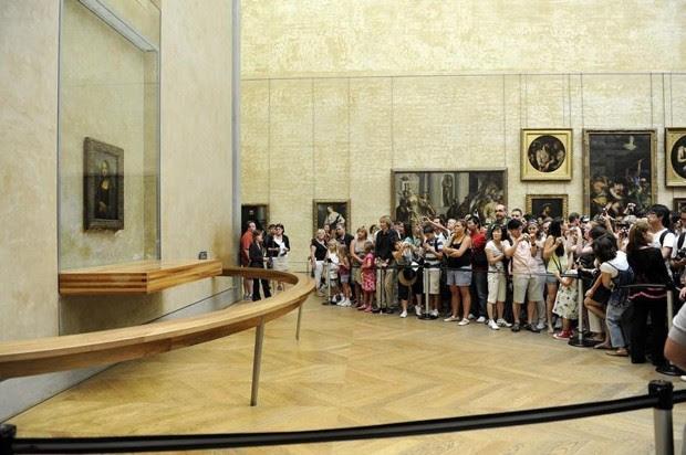 """Turistas atrás de cordão de isolameto para observar quadro """"Mona Lisa"""" no Museu do Louvre, em em Paris, em foto de 2009  (Foto: Reuters/Jacky Naegelen)"""