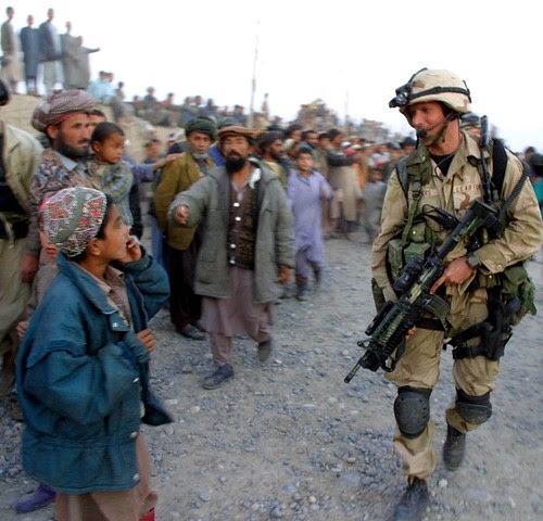 At sundown, a United States Air Force Special Operations soldier walks by an Afghan boy as others loyal to the rebel Northern Alliance look on