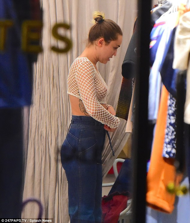 Shopping spree: The 23-year-old checked herself out in the mirror as she tried on a pair of jeans