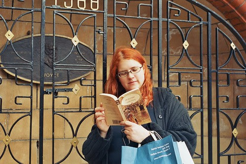 photo of a librarian reading Joyce in front of the Joyce memorial in Dublin's St Patrick's park