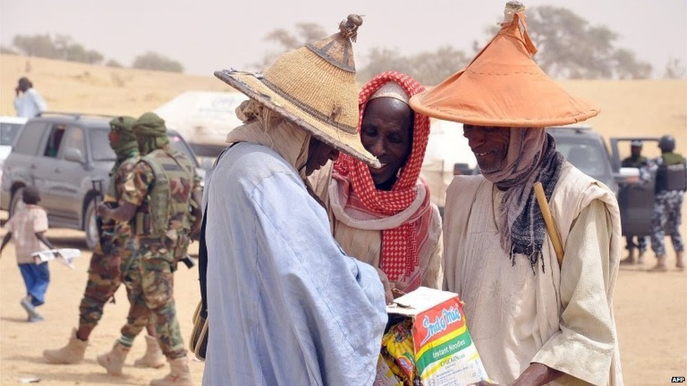 Elderly men fleeing from Boko Haram attacks tries to share food items distributed at Kabalewa Refugees Camp, Diffa in Niger Republic, on 13 March  2015