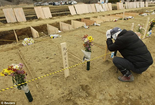 Grieving: A man pays his respects at the temporary mass grave site