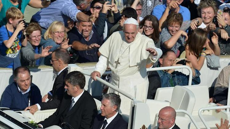 Pope Francis greets the crowd at St Peter's square after a mass on October 27, 2013 at the Vatican